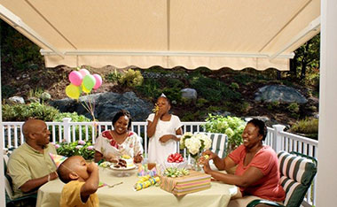 Family celebrating a birthday under an awning